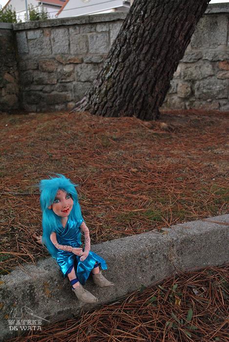 muñeca de hadita turquesa de trapo sentada en el bosque